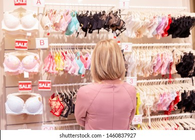 Young woman chooses underwear in the store. A large assortment. Close-up.
