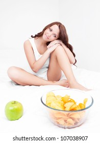 young woman choosing between an apple and potato chips in bed at home