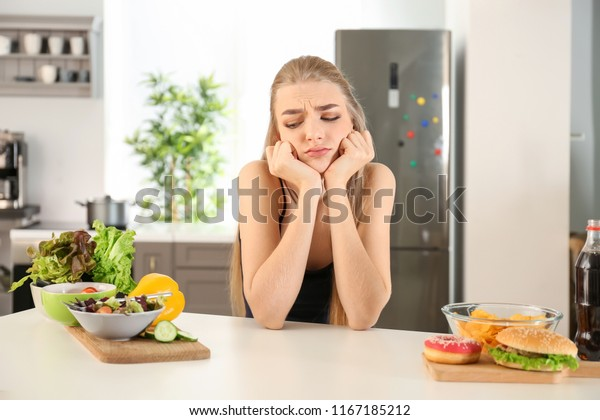 Young woman choosing between diet and unhealthy food in kitchen