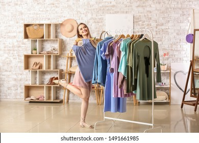 Young woman choosing clothes in dressing room