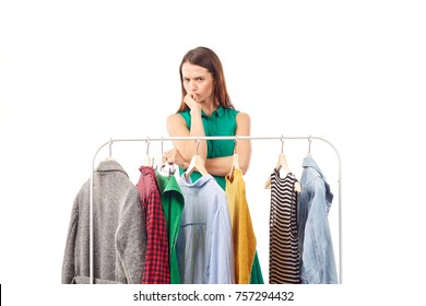 Young woman choosing clothes on rack on white background