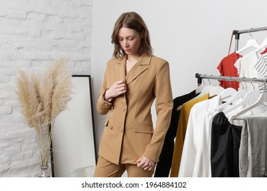Young woman choosing clothes and trying on beige blazer in fashion atelier or personal wardrobe.