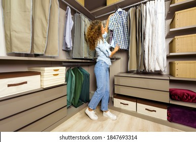 Young woman choosing clothes to wear off the rail in a fitted neat walk-in closet looking at a checked shirt on a hanger