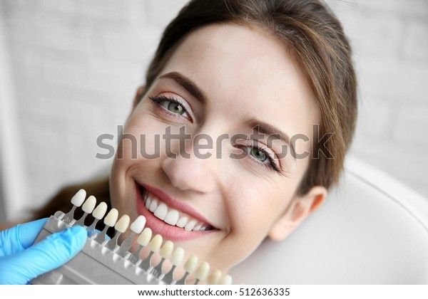 Junge Frau, die sich für Zahnfarbe beim Zahnarzt entscheidet