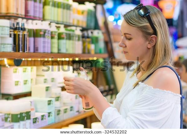 Jeune femme choisissant une crème cosmétique dans un salon de beauté.