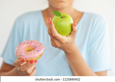 Young woman choosing to eat a healthy green apple fruit instead of attractive hyper caloric donut