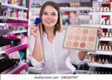 Young woman choosing face powder at cosmetic shop, testing before buying