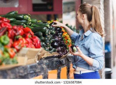 young woman is choosing fresh aubergine in the market.