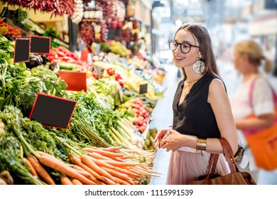 Young woman choosing goods standing at the counter with a bunch of different fresh food in theGreat Market hall in Budapest