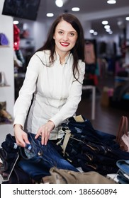 Young Woman choosing jeans at clothing store