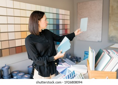 Young woman choosing materials for home renovation. interior designer looking at color samples for wal. House renovation concept