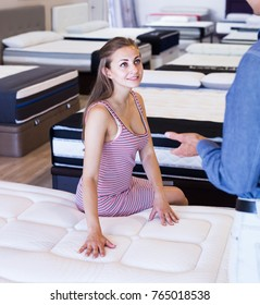 Young woman choosing new mattress in furniture office