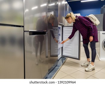 young woman choosing new refrigerator in household appliances store