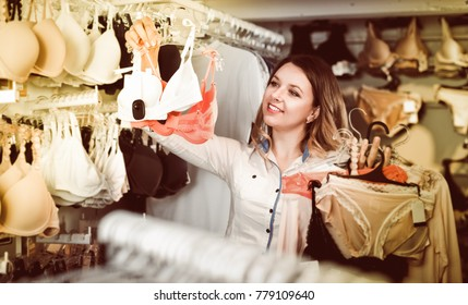 Young woman choosing pretty clothing in lingerie shop