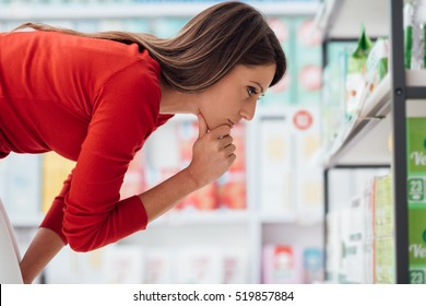 Young woman choosing products on the supermarket shelves and reading labels, she is thinking with hand on chin
