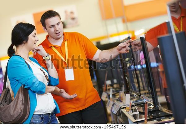 Junge Frau, die sich für Fernseher mit Ladenassistentin im Einkaufszentrum für Haushaltsgeräte Supermarkt