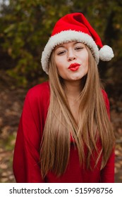 Young woman with Christmas hat and red lips in the forest