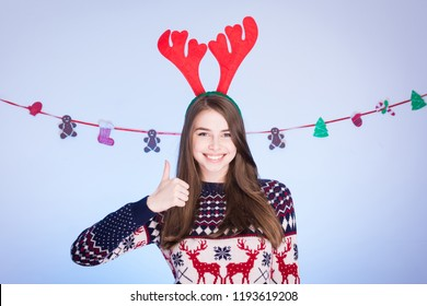 Young woman in Christmas outfit, gesturing thumbs up and smiling. Closeup, studio lighting.