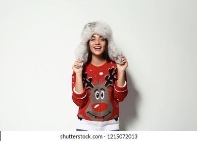 Young woman in Christmas sweater and hat on white background