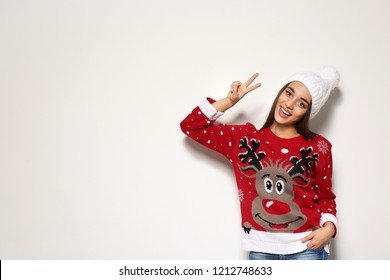 Young woman in Christmas sweater and knitted hat on white background. Space for text