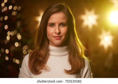 Young woman with christmas tree and lights in background.