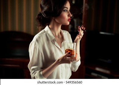 Young woman with cigar and glass of whiskey in retro atmosphere. She smokes cigar and blows smoke.