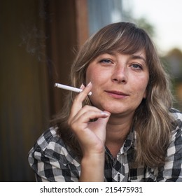 Young woman with a cigarette, outdoors. Close-up portrait.