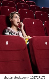 Young woman in the cinema hall side view