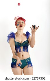 Young woman circus performer juggling balls in the air