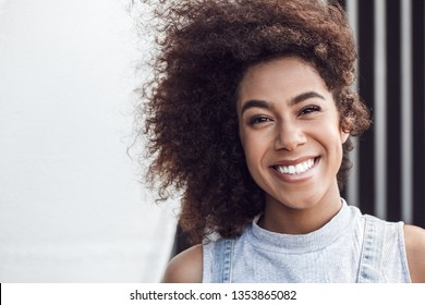 Young woman in the city street standing leaning on wall looking camera laughing playful close-up