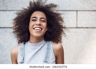 Young woman in the city street standing isolated on concrete wall looking up laughing joyful close-up