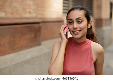 Young woman in city talking on cell phone