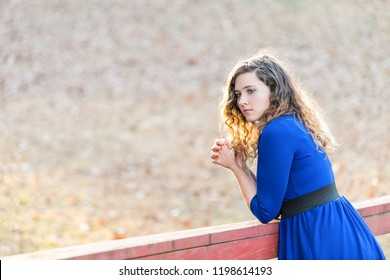 Young woman with clasped hands, praying prayer, standing in nature on wooden red painted bridge over creek, river during sunset in autumn, winter with backlight, backlit hair