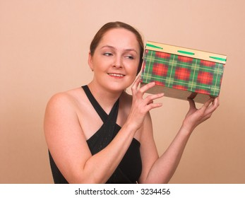Young woman clasping present box to her ear smiling
