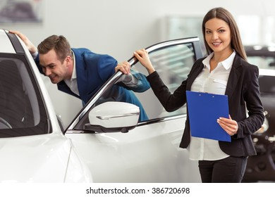 Young woman in classic suit is smiling and looking at camera while handsome young customer is examining a car in a motor show