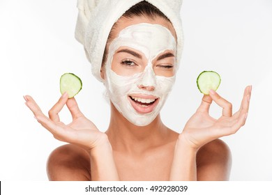 Young woman with clay facial mask holding cucumber slices isolated on white background