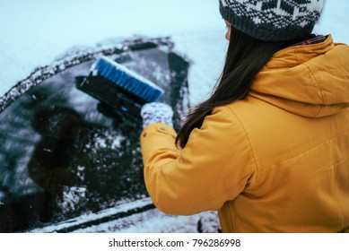 young woman clean car after snow storm with scraper
