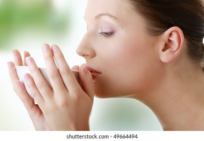 Young woman with clean face drinking green tea - spa concept.