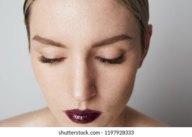 Young woman with clean skin, natural make-up over empty white background. Close-up portrait