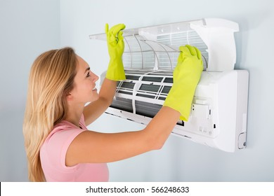 Young Woman Cleaning Air Conditioning System At Home