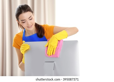 Young woman cleaning computer monitor at workplace in the office