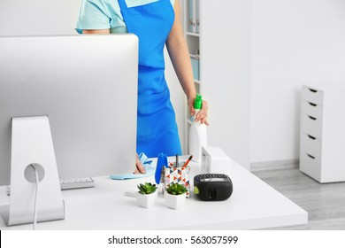 Young woman cleaning computer table in office