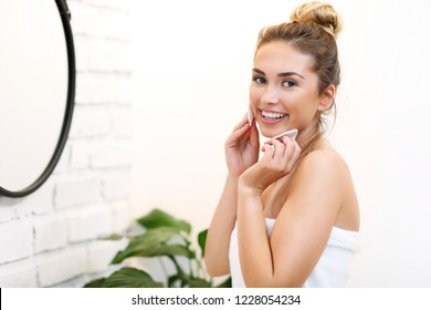 Young woman cleaning face in bathroom mirror