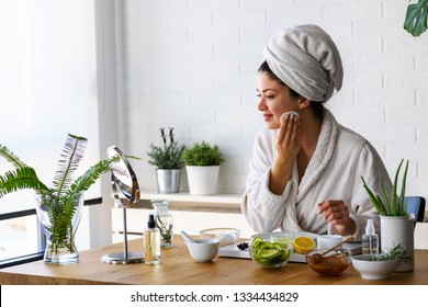 Young woman cleaning face with natural cosmetics. How to get clear and glowing skin
