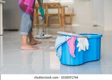 Young woman cleaning floor in living room with mop and bucket, Housework concept