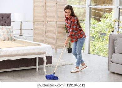 Young woman cleaning floor with mop in bedroom