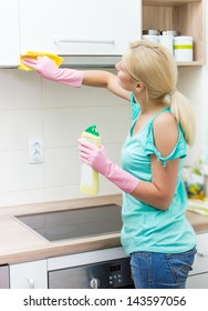 Young woman cleaning furniture in the kitchen.