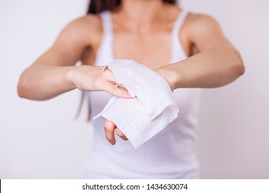 Young woman cleaning hands with wet wipes, white