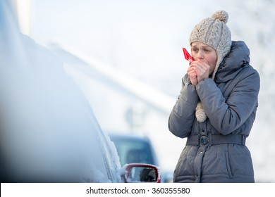 Young woman cleaning her car from snow and frost on a winter morning, she is freezing and needs to get to work