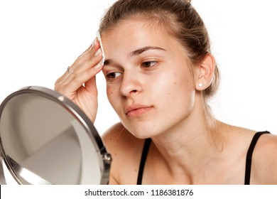 Young woman cleaning her face with wet cotton pade on white background